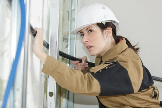 female electrician fitting conduit in wall at construction site