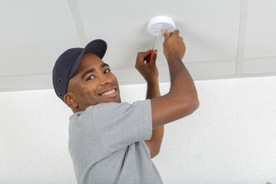 electrician removing battery from smoke detector